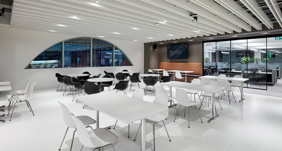 Scalar lunchroom with dome shaped window, white floor and ceiling, and black and white chairs at white tables
