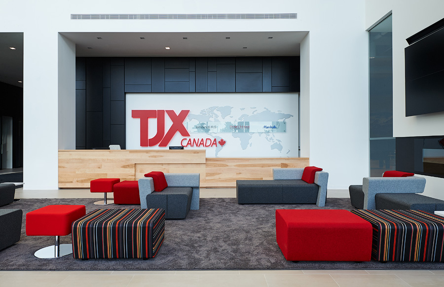 TJX reception with red TJX logo on wall, natural wood desk, and upholstered seating