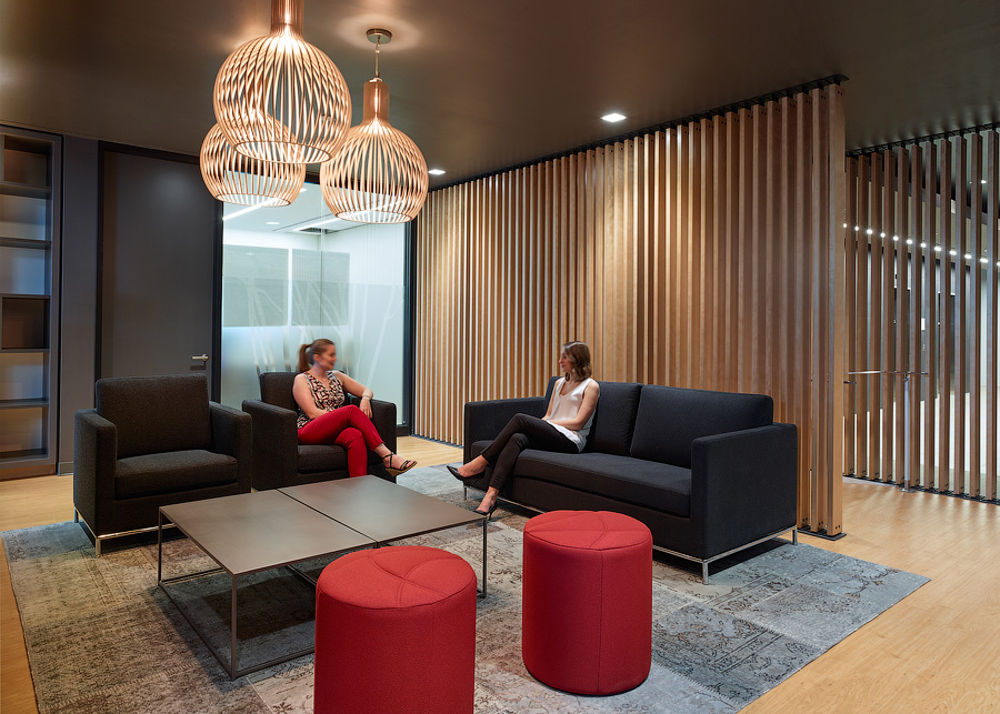 TJX seating area with dark grey sofa and chairs, red ottomans, and wood slat divider walls