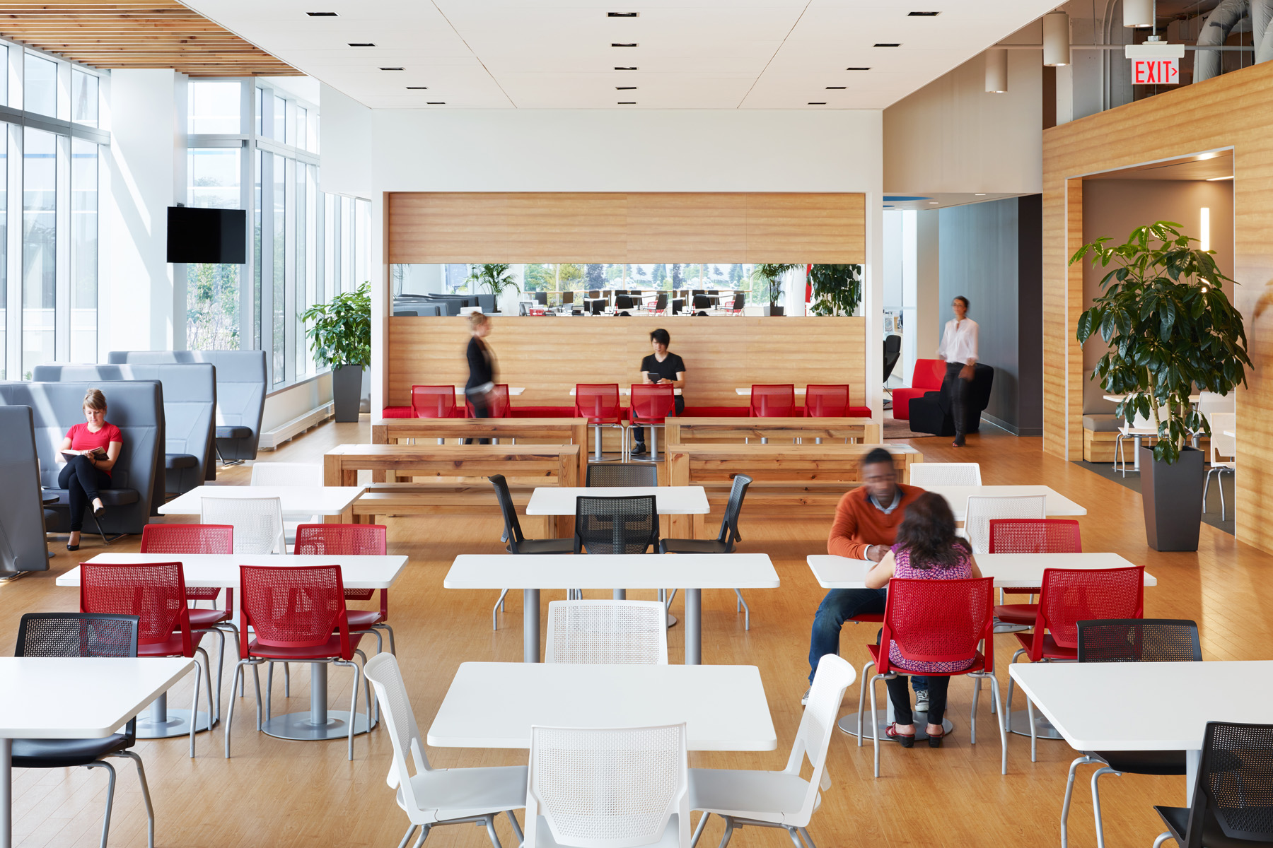 TJX cafeteria with natural wood floors and walls, white and red tables and chairs, and dark grey booths