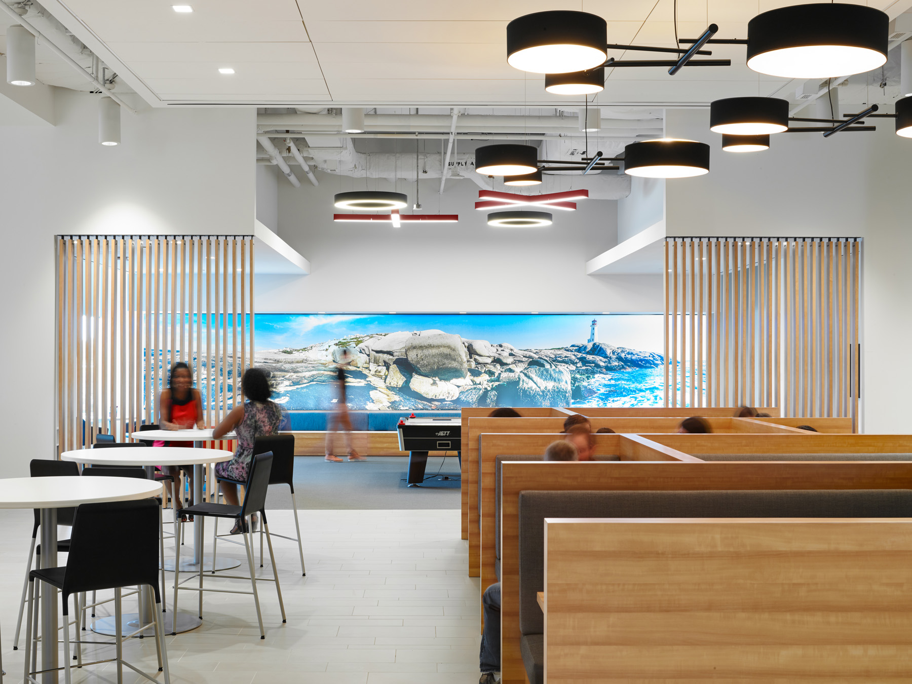 TJX lunchroom with wooden booths, air hockey table, and photographic panorama mural of rocky landscape on wall