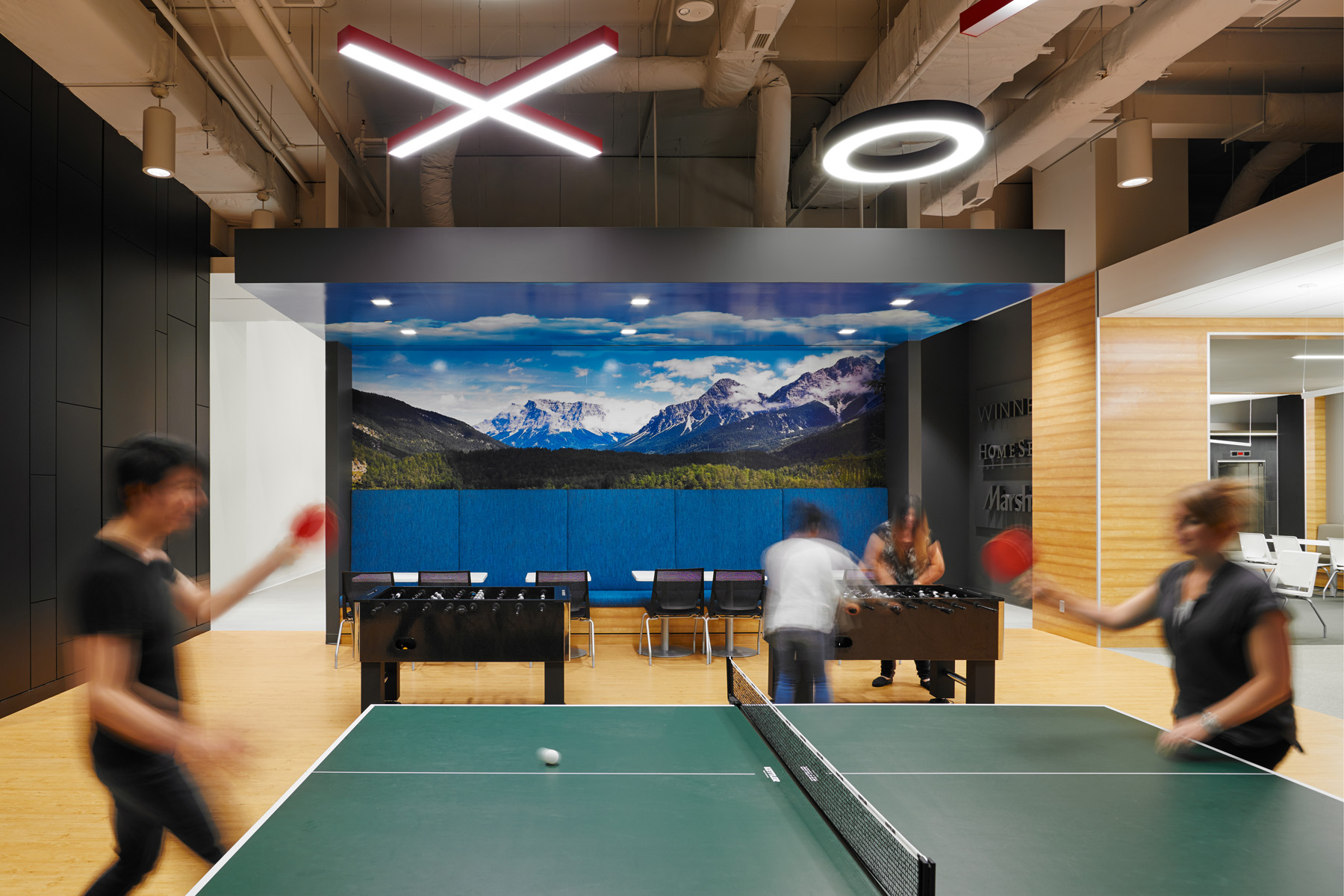 TJX game room with photo mural of mountains on wall, and people playing ping pong