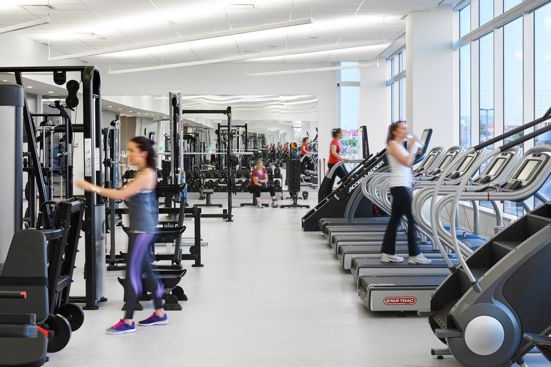 TJX employees using equipment in gym with large windows