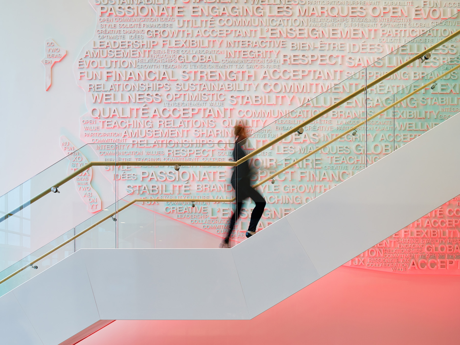 TJX woman walking up staircase with white and pink graphic text collage on wall