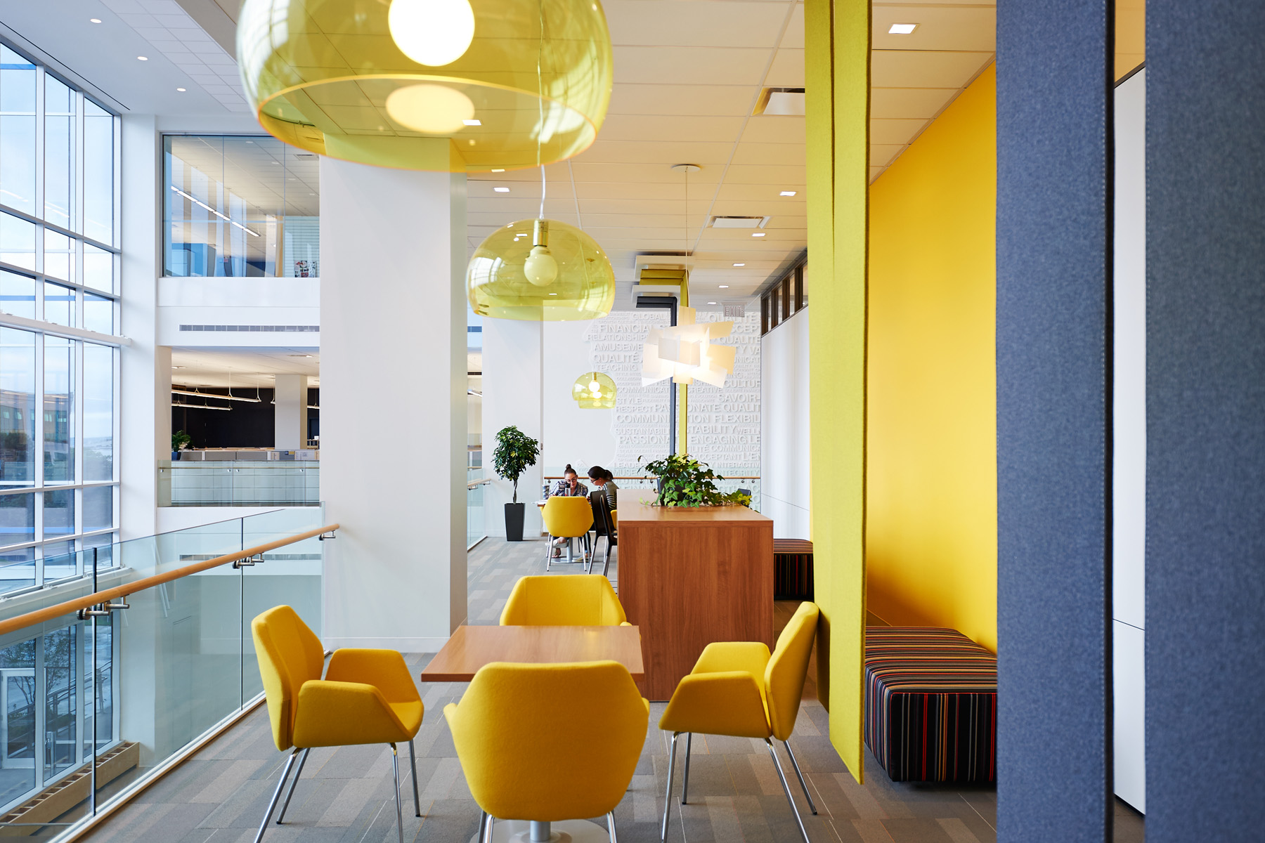 TJX seating area with yellow chairs, yellow and white walls, and yellow glass dome light fixtures