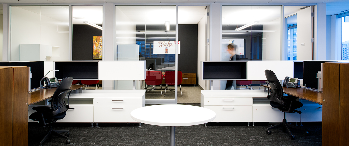 Coca Cola workstations in front of private offices with glass walls