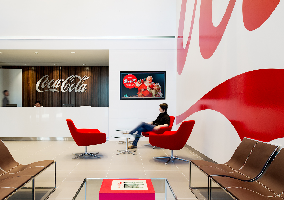 Coca Cola reception seating area, with wood wall and silver Coca Cola logo, white walls and red armchairs