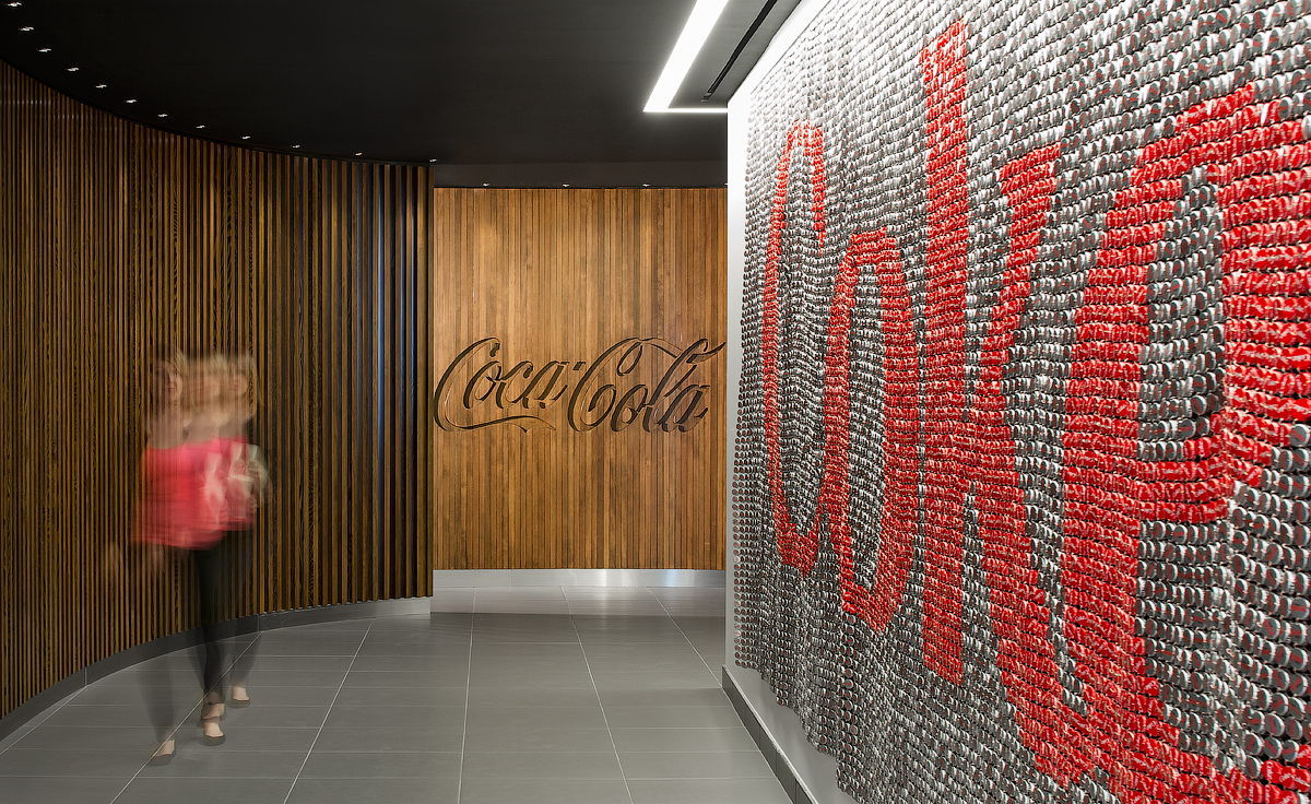 Coca Cola walkway featuring wood wall engraved with logo, and art piece made up of bottle caps forming Coca Cola logo