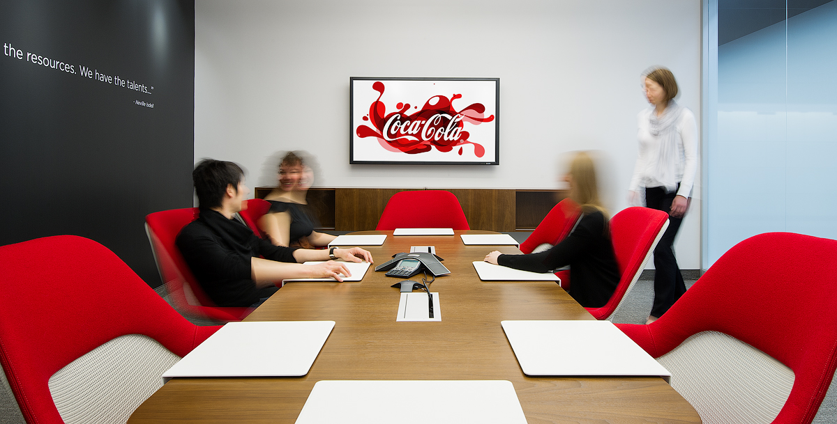 Coca Cola meeting room with wood table, red chairs, and screen showing Coca Cola logo