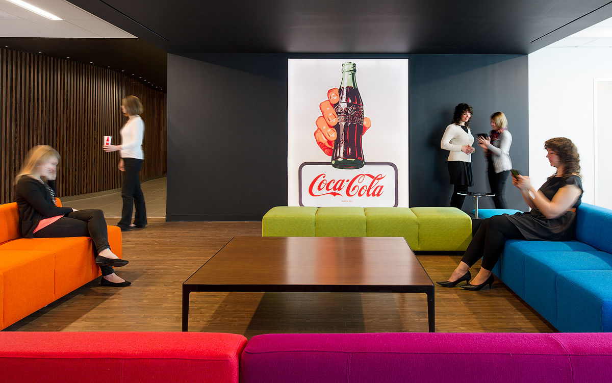 Coca Cola seating area with vintage Coca Cola ad poster, black walls, and colourful upholstered seating