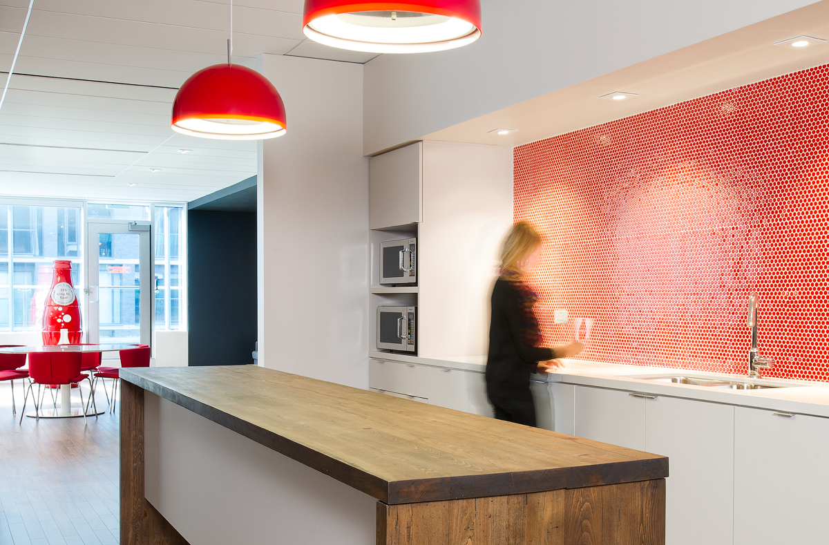Coca Cola kitchen with white cabinets, wood island, red backsplash, and red domed pendant lights