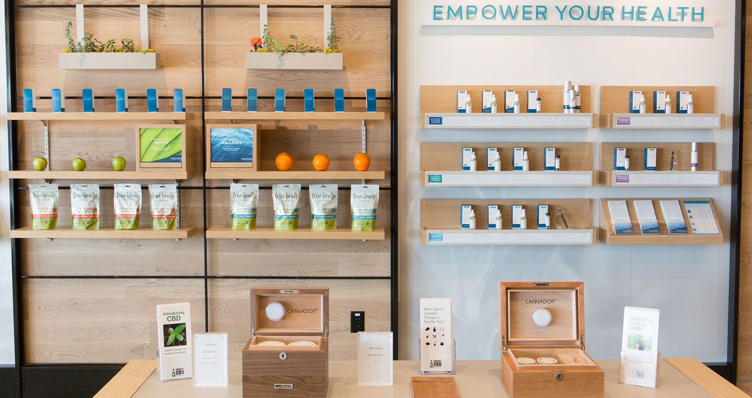 Surterra wall with products displayed on wood shelves and table in front
