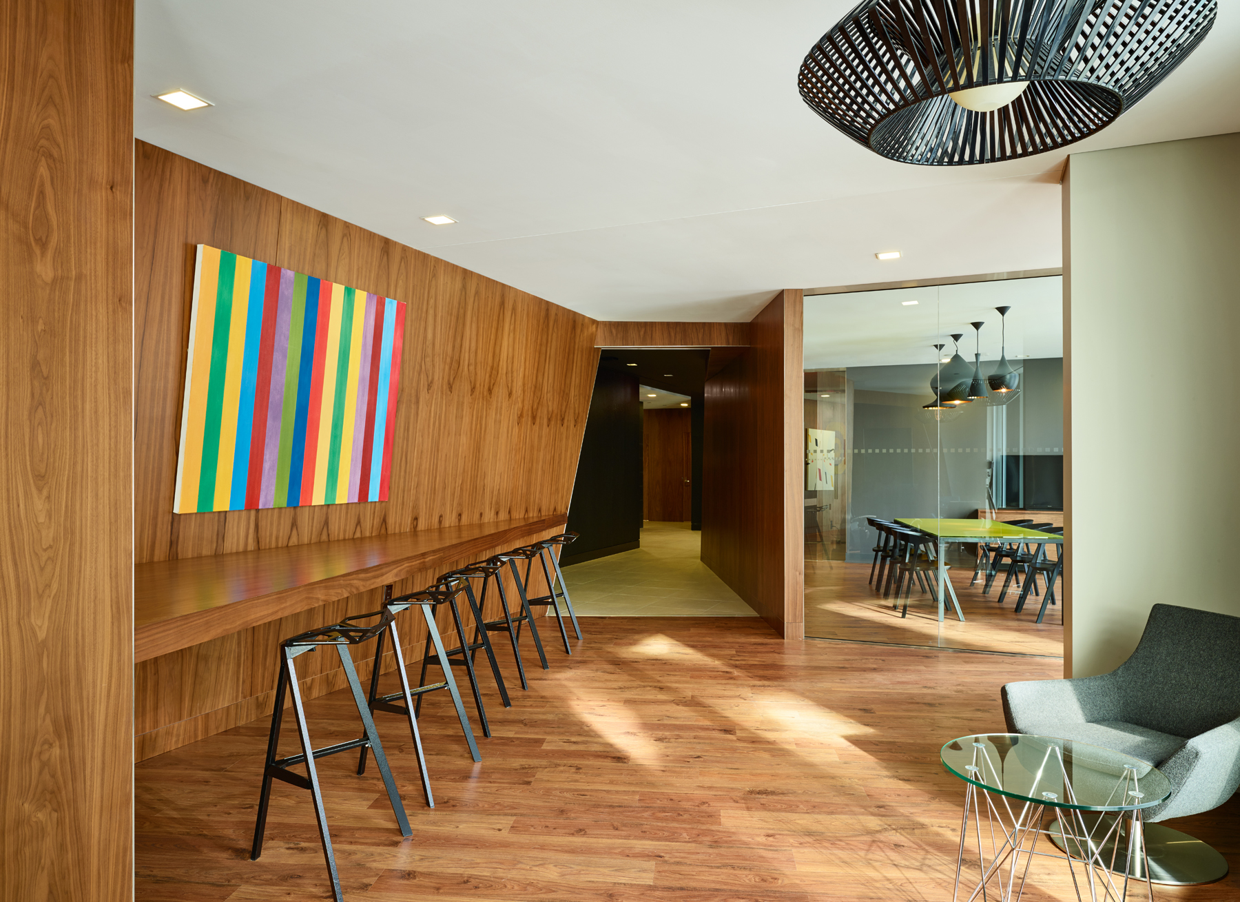 Concord Quartz communal space seating area with wood walls, wood floors, black stools, and colourful abstract artwork
