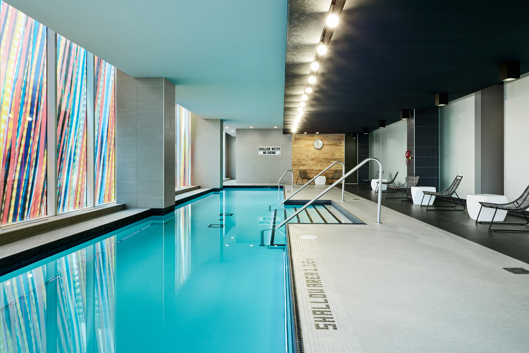 Concord Quartz pool with bright blue water, white tile floor, black ceiling, and colourful glass wall