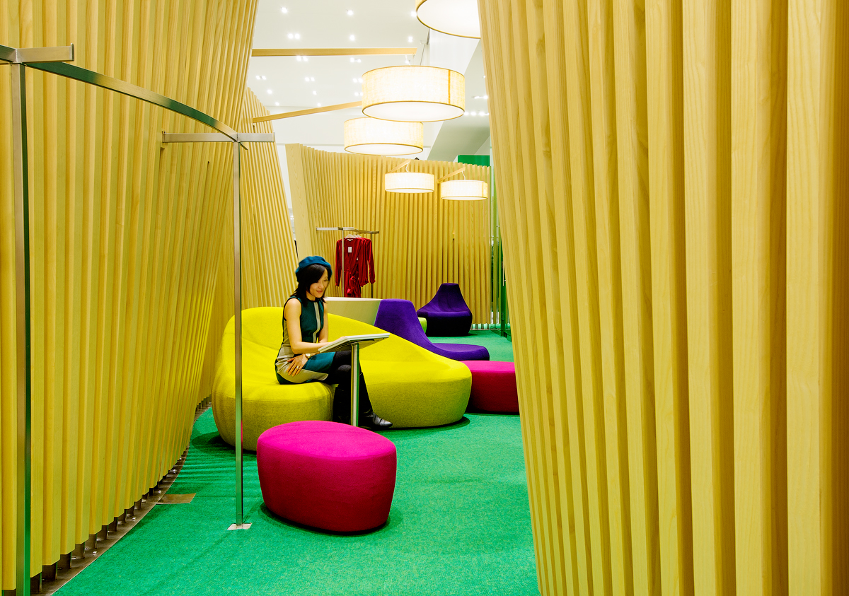 La Maison Simons women's fitting room with green carpet, colourful seating, and yellow wood room dividers