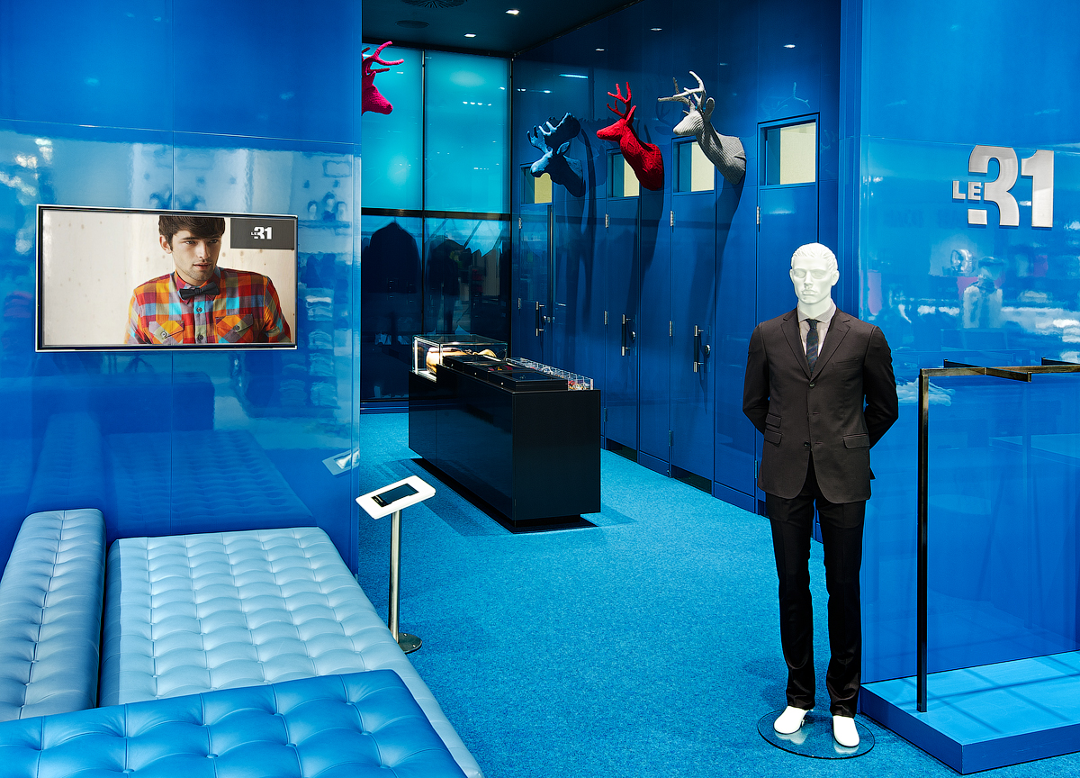 La Maison Simons fitting room with blue walls, blue seating, and blue carpet