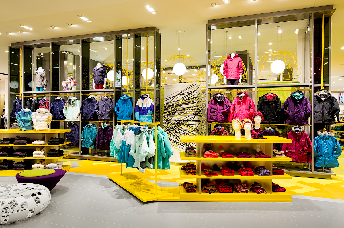 Simons outerwear display with yellow shelves and glass walls