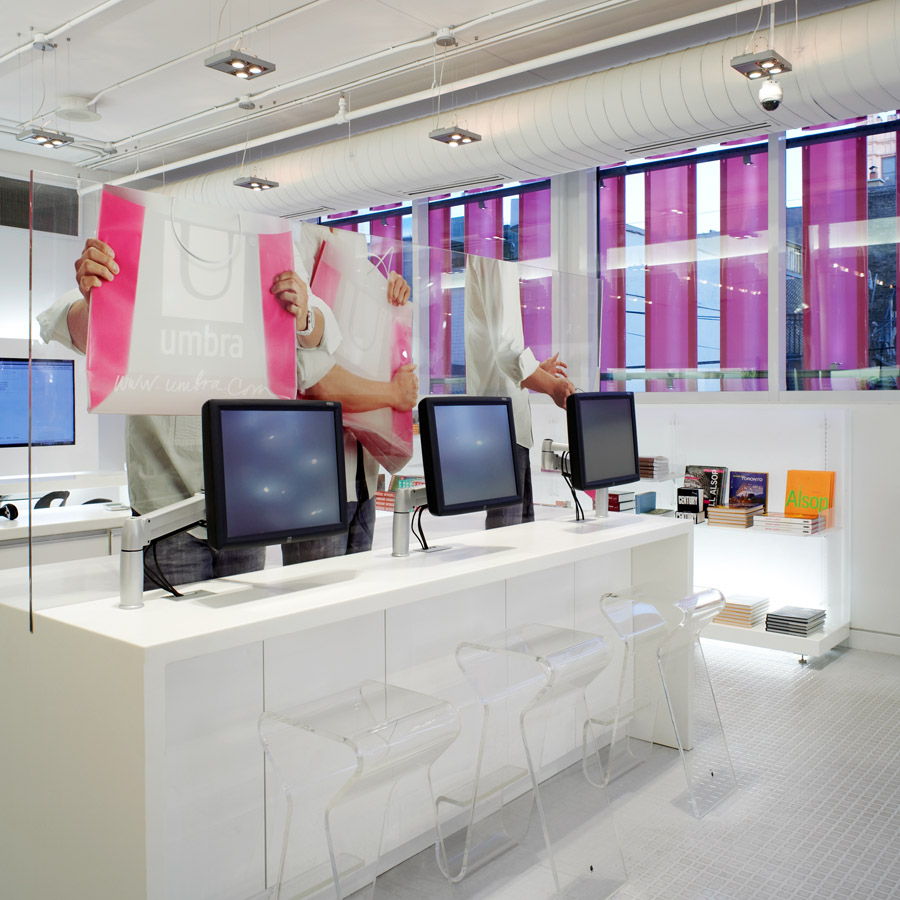 Umbra Toronto, white gallery desk with computer screens, bookshelf, and glass partition