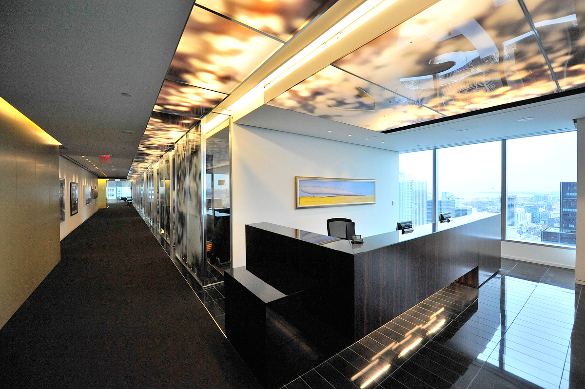 Goodmans lobby with black tile floor, dark wood reception desk, and gold patterned ceiling