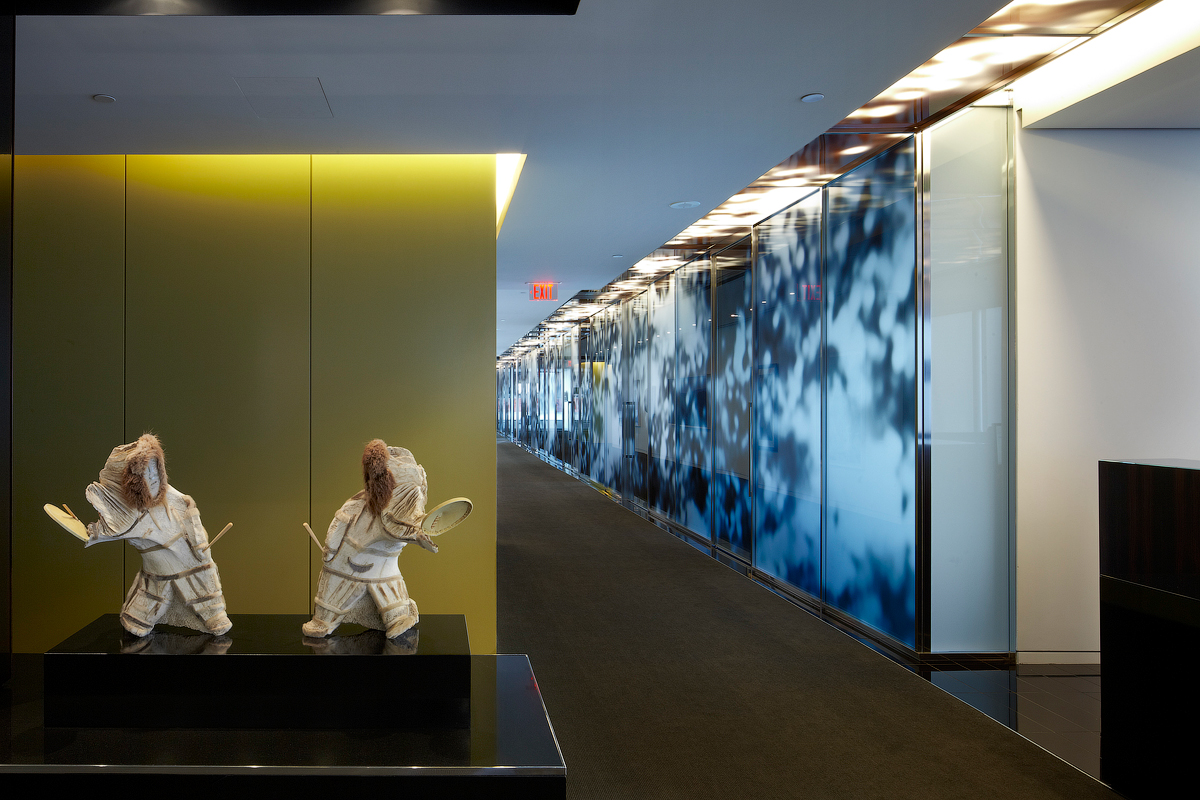 Goodmans closeup of Indigenous sculptures in front of gold wall, next to hallway with patterned glass wall