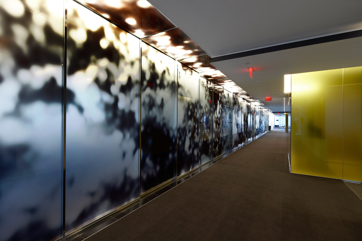 Goodmans hallway with gold wall across from abstract patterned glass wall