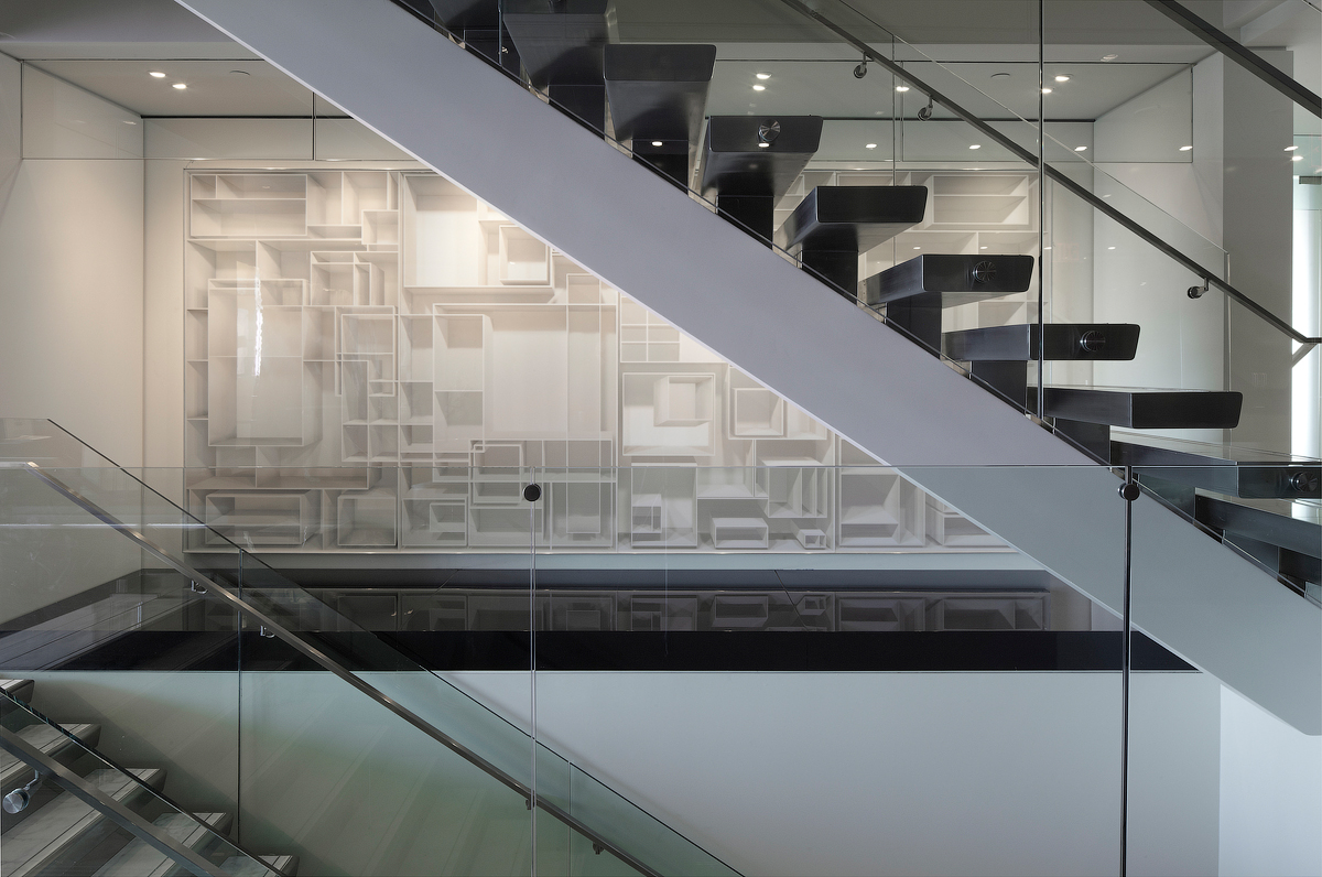Goodmans staircase with glass walls, silver railings, and white sculptural wall