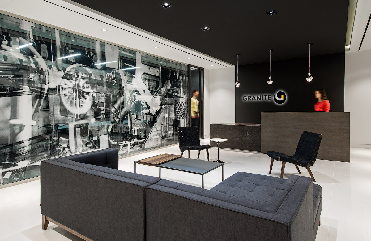Granite Toronto lobby with Granite logo on black wall, dark wood desk, grey sectional, and graphic glass wall