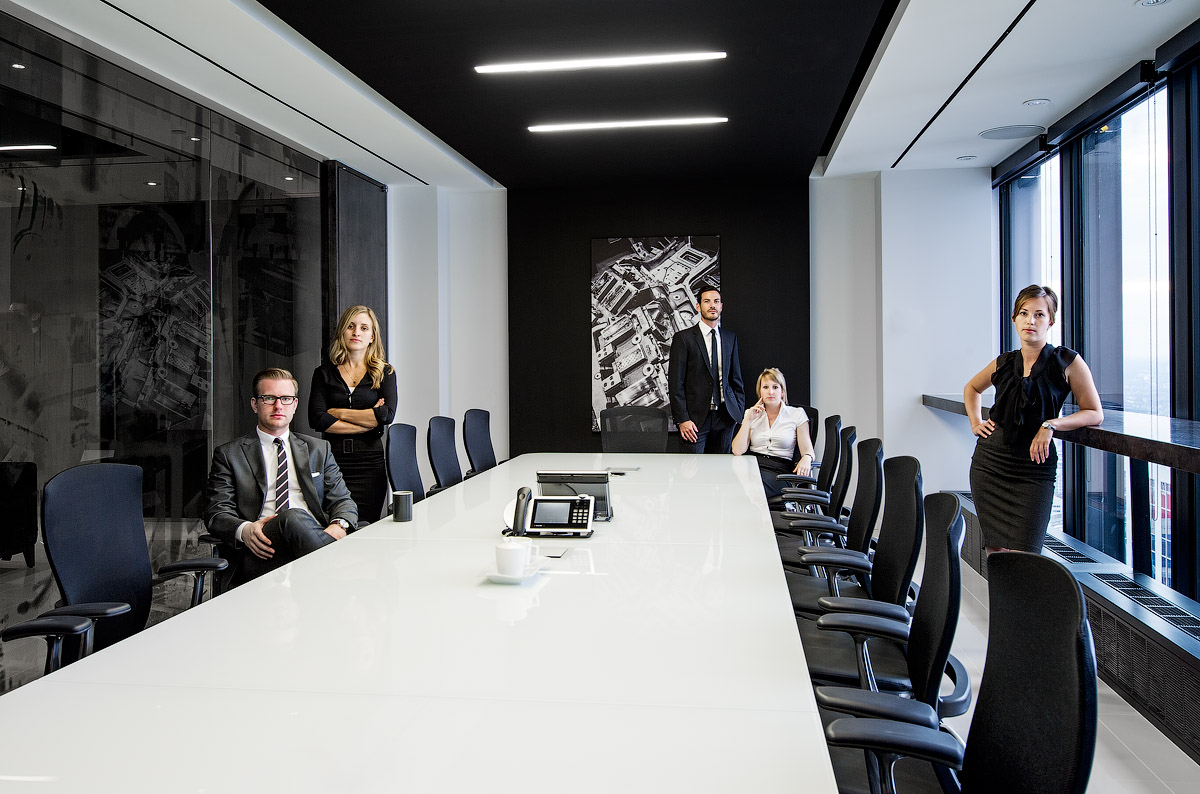 Granite Toronto meeting room with white conference table, black chairs, and black and white abstract artwork