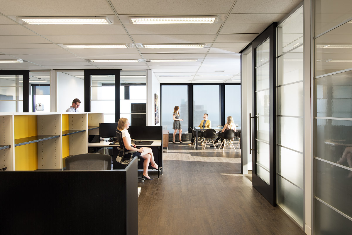 Granite Toronto workspace with frosted glass meeting room walls and dark wood floors