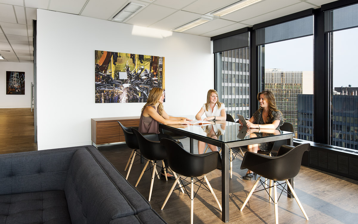 Granite Toronto, three women sitting at informal meeting table in front of window, with black chairs and abstract artwork
