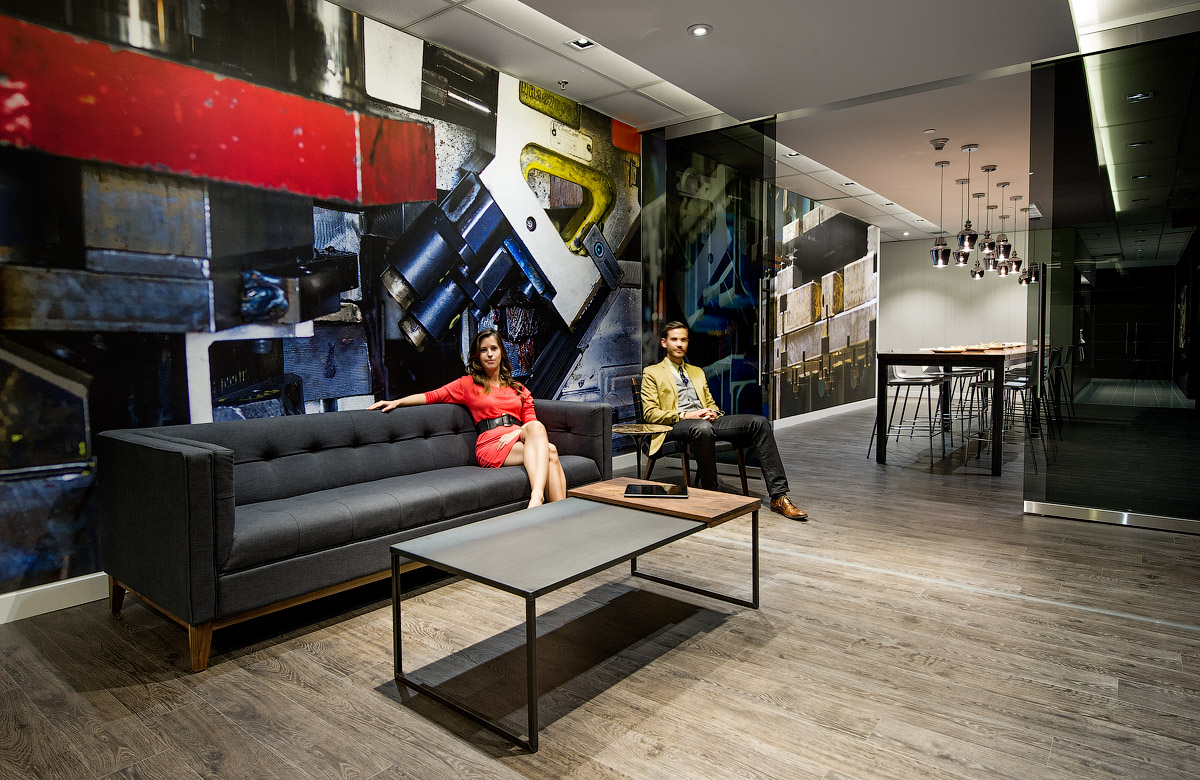 Granite Toronto seating area with grey sofa, distressed wood floors, and abstract graphic wall in red, black, and yellow