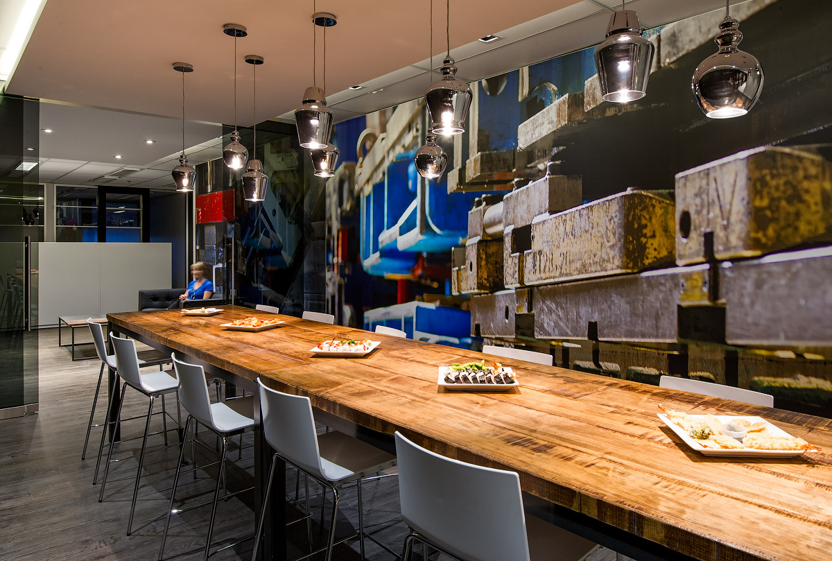 Granite Toronto social zone with long wood table, industrial pendant lights, and abstract graphic wall in blue, black, and grey