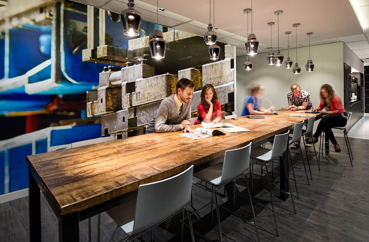 Granite Toronto social space with wood table and abstract graphic wall in blue, black, and grey