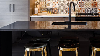 Great Gulf Westfield kitchen detail of black marble island and brass stools