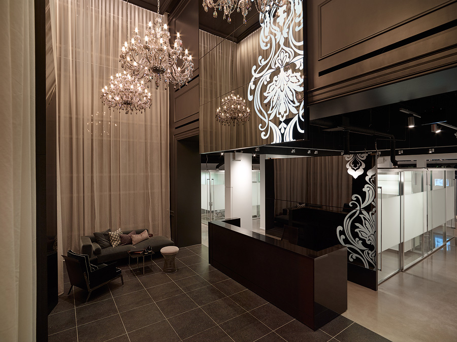 Great Gulf Idea Centre lobby with reception desk, floor to ceiling curtains, sofa, and two chandeliers