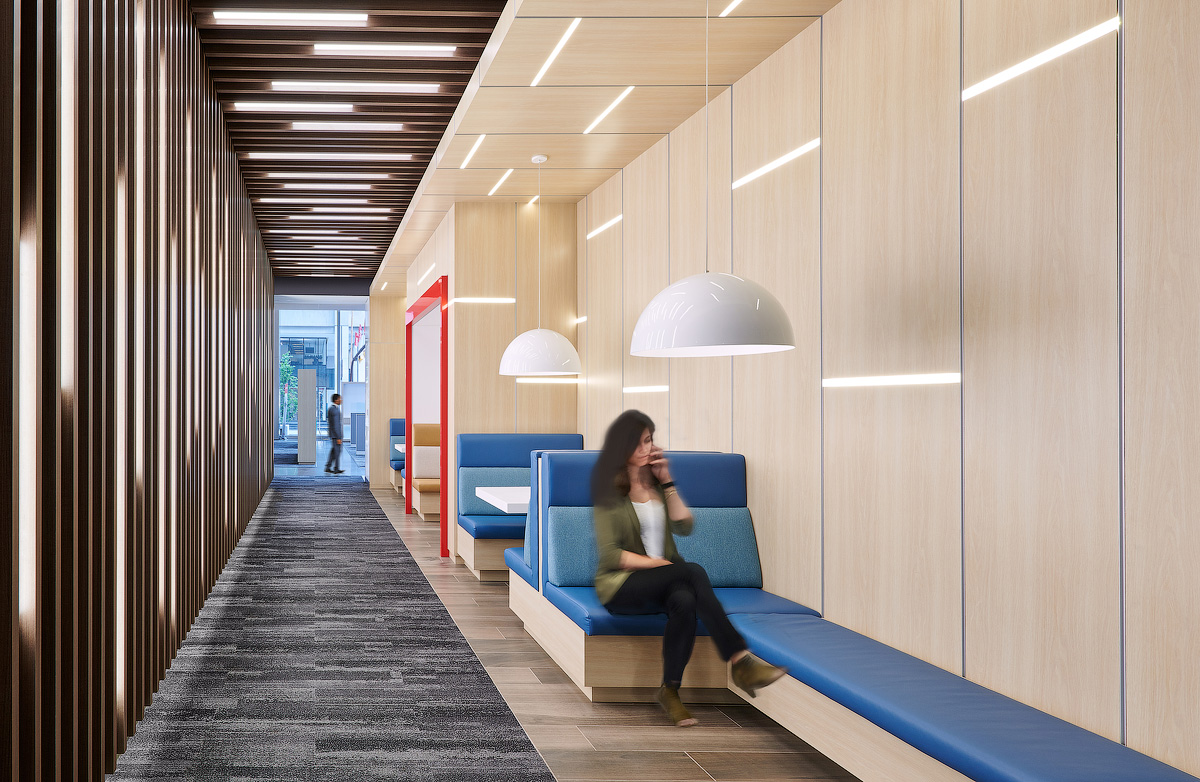 Scotiabank Calgary seating area with light wood walls and blue upholstered bench seating