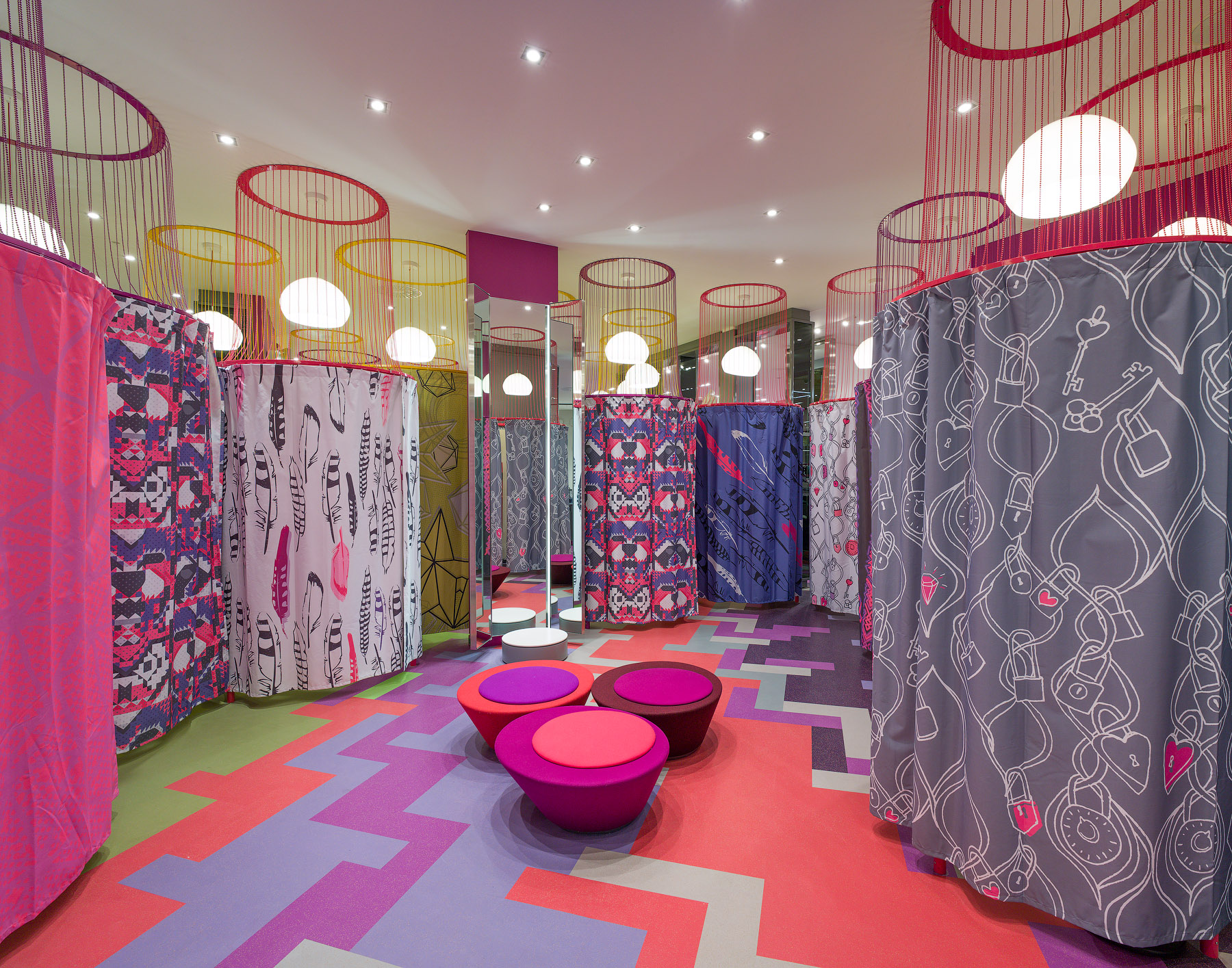 La Maison Simons fitting room with patterned curtains and floor in purple, pink, and orange