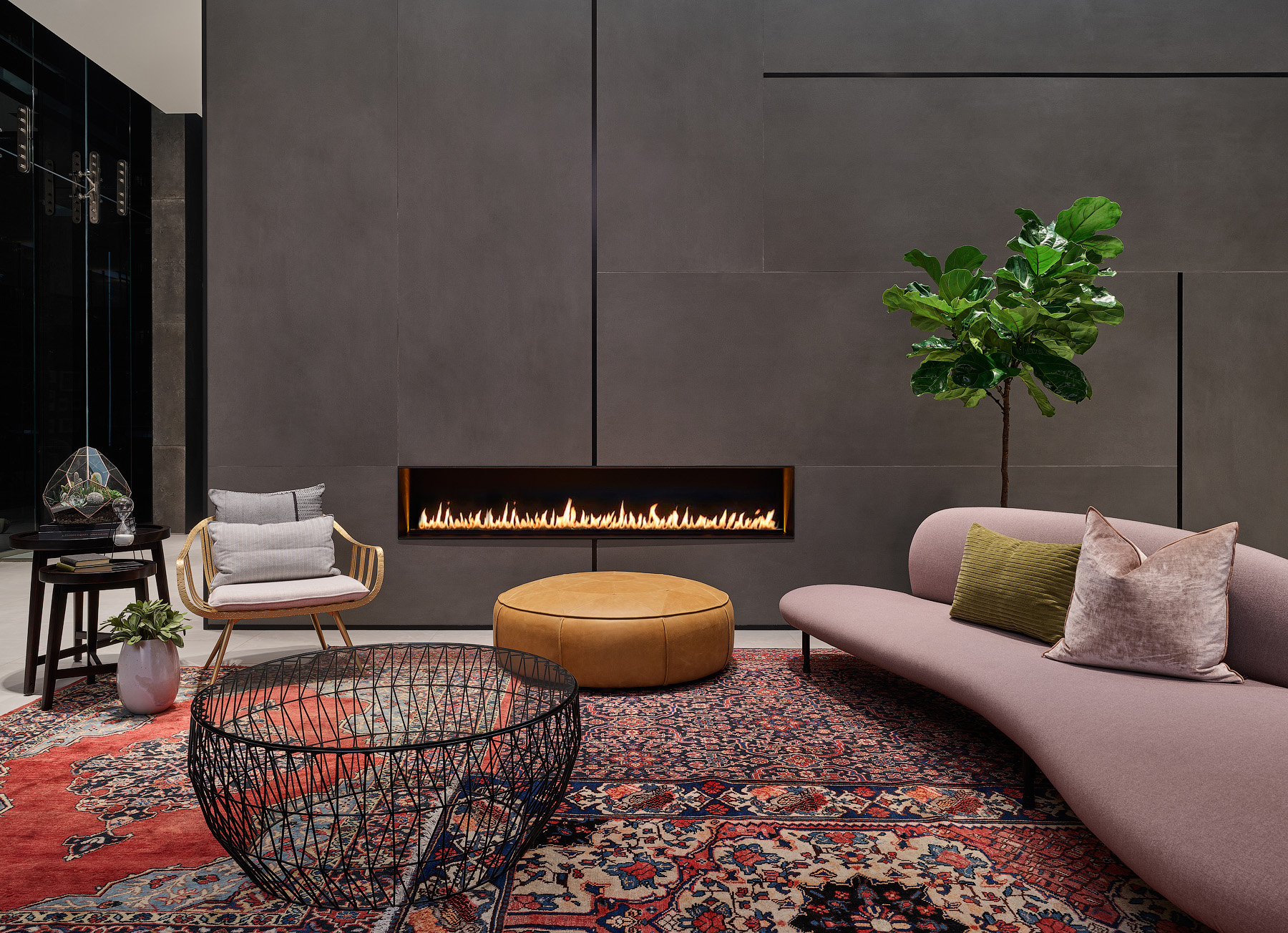 Empire Phoenix seating area with large charcoal tile wall, contemporary fireplace, blush pink sofa, and Persian rug