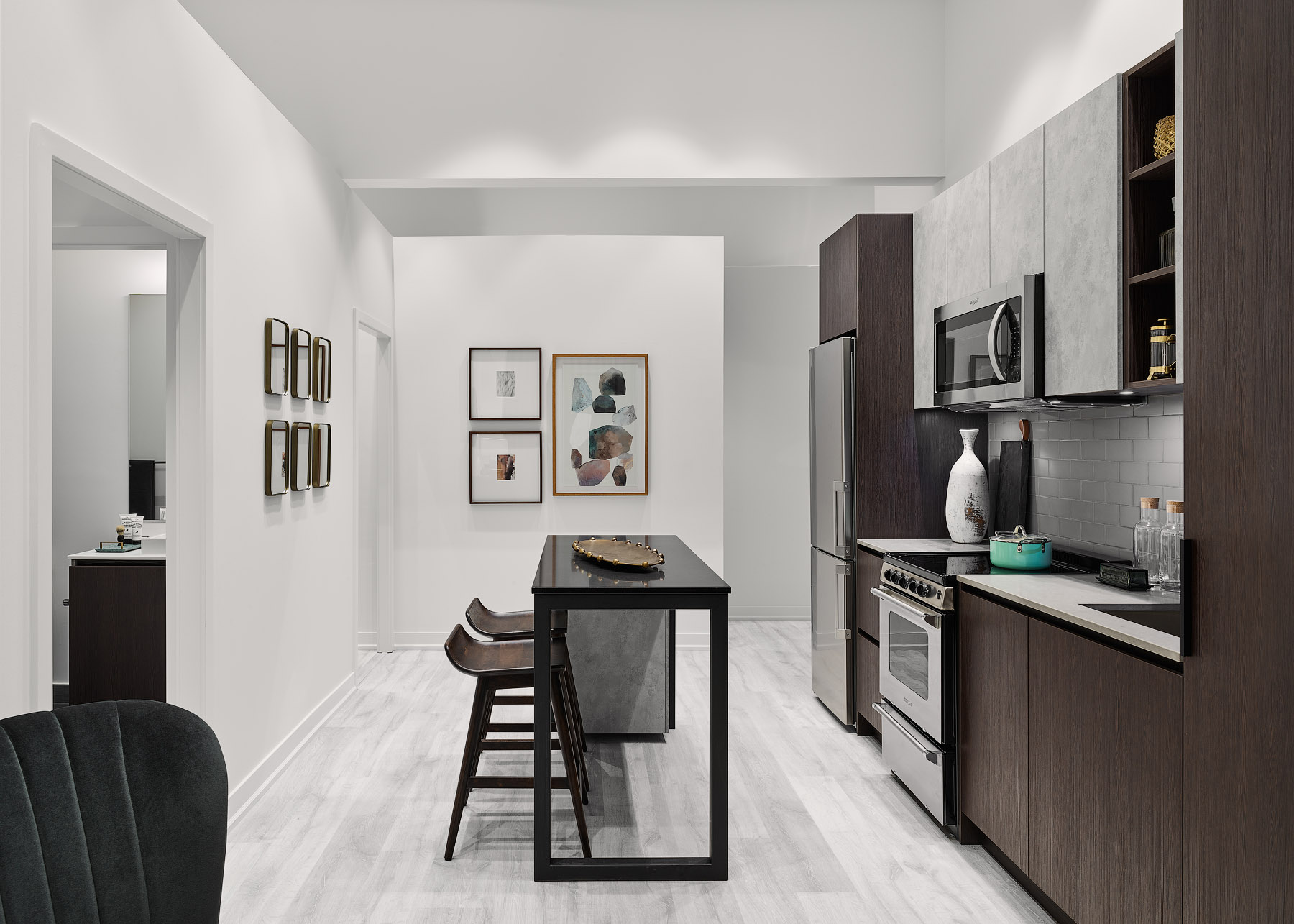 Empire Phoenix kitchen with white walls, dark brown cabinets, and island with bar stools