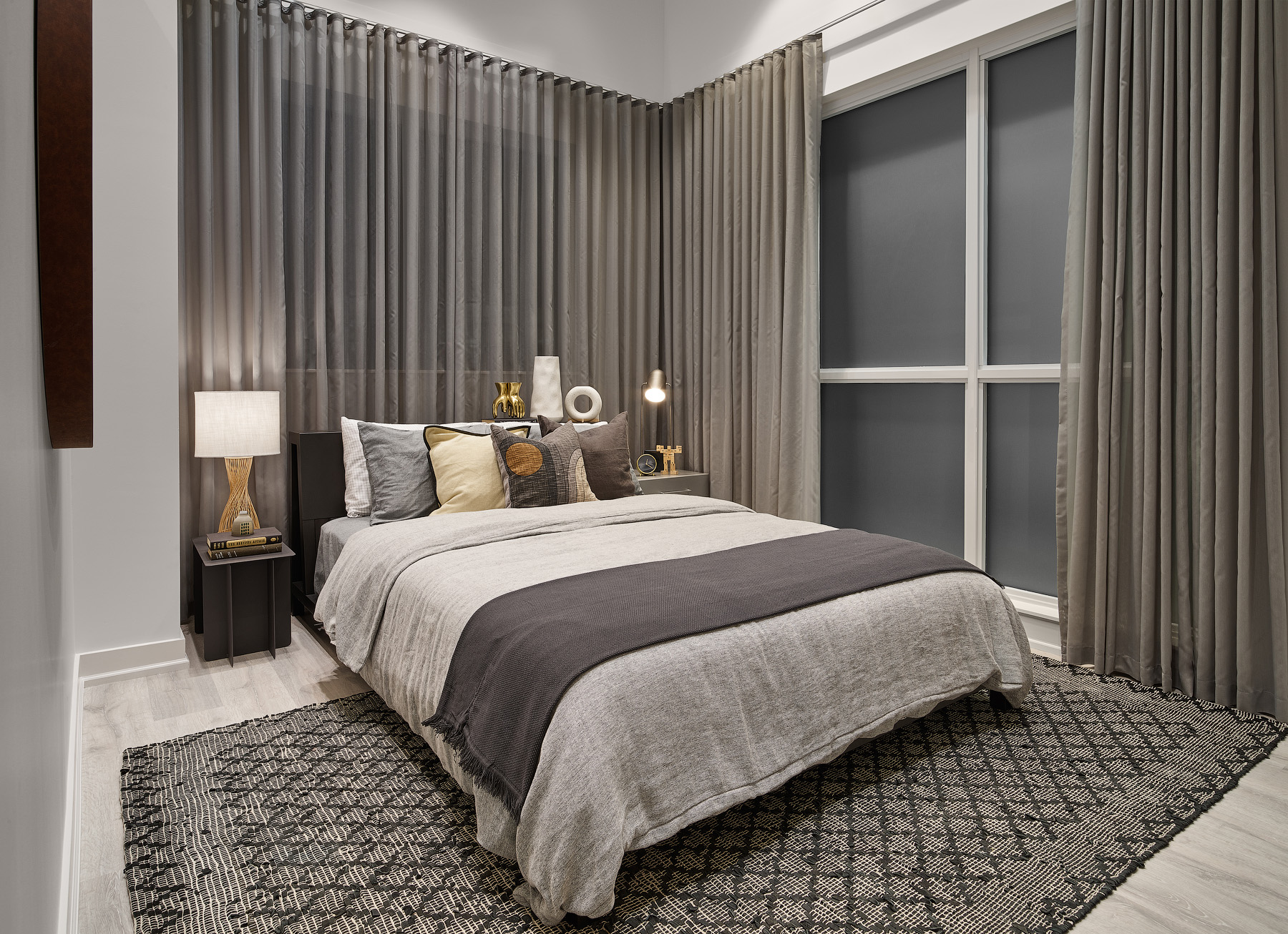 Empire Phoenix bedroom with large windows, grey curtains, and layered linen bedding