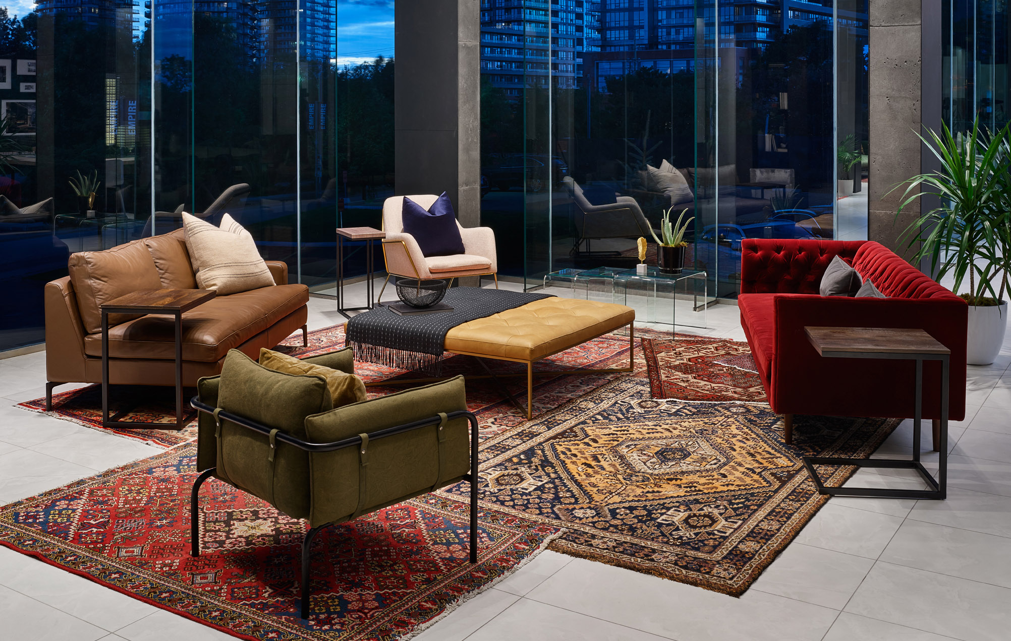 Empire Phoenix lobby with bright red sofa, layered Persian rugs, and large windows