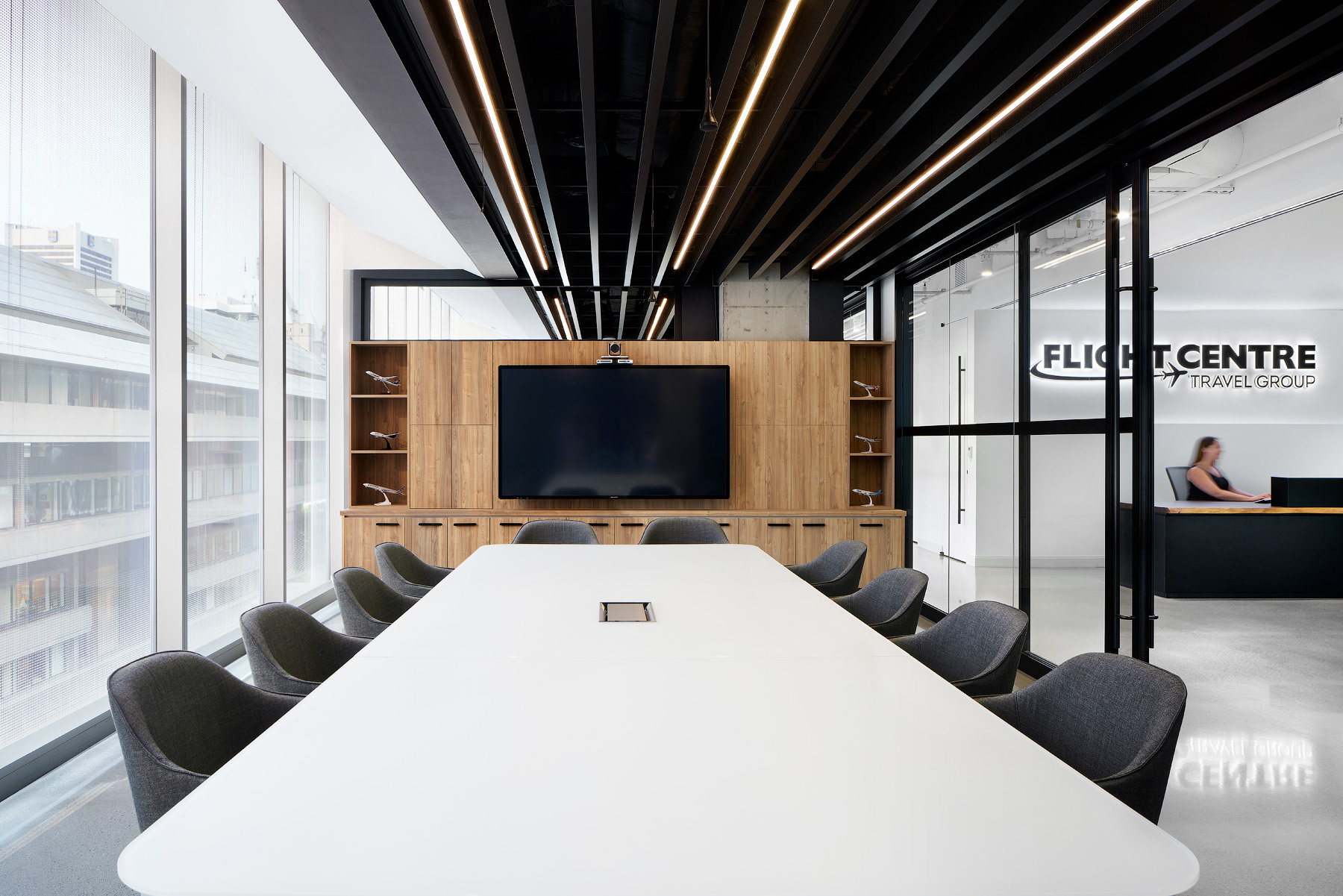 Flight Centre Vancouver conference room with large table, black ceiling panels, and wood wall with television