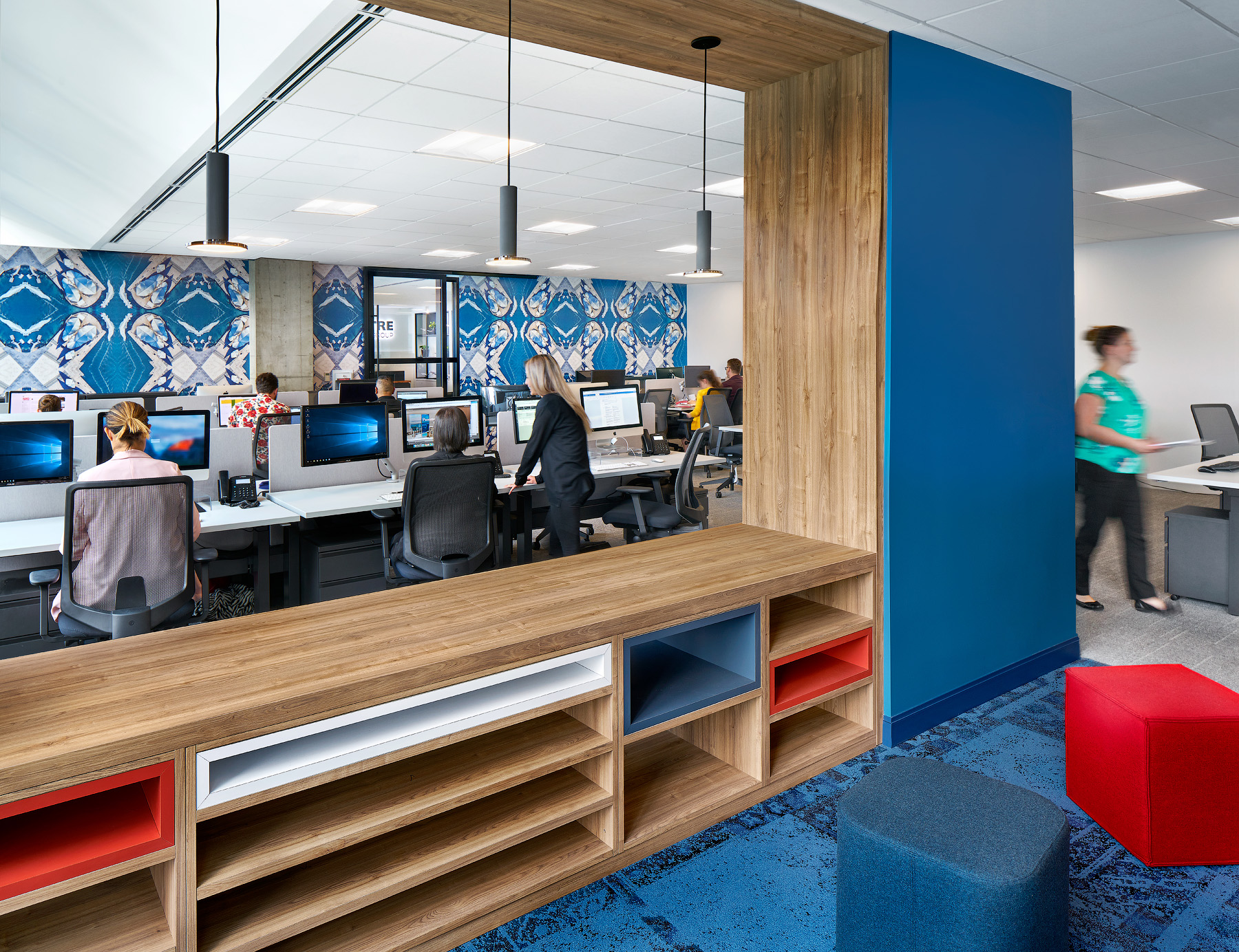 Flight Centre Vancouver work stations with people at desks, patterned wallpaper, and wood shelving with blue accents