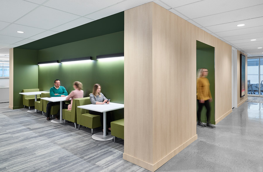 GWL-RA office social zone with light wood walls and alcove with green walls and seating