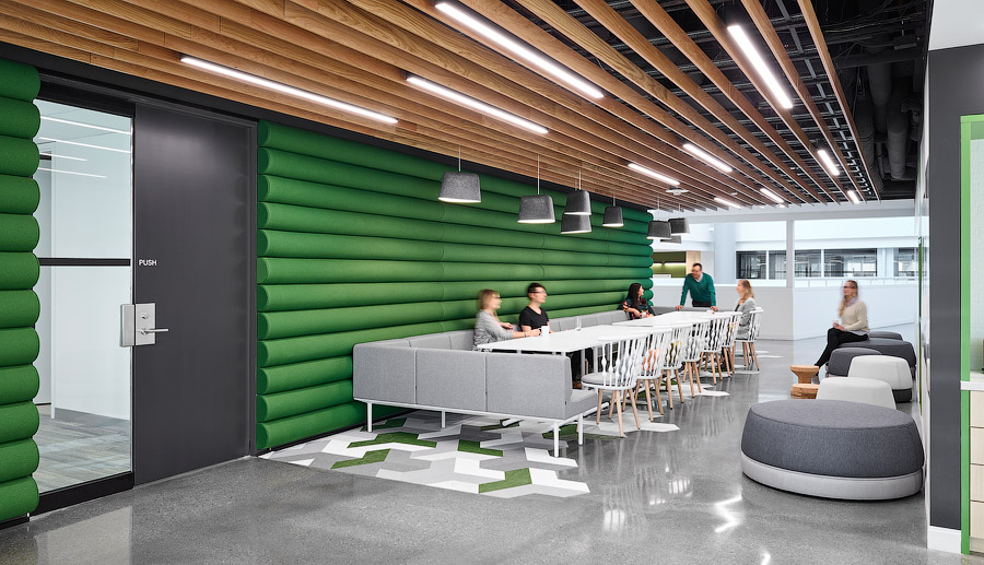 GWL-RA office seating area with green upholstered wall, wood ceiling, tables, and ottomans