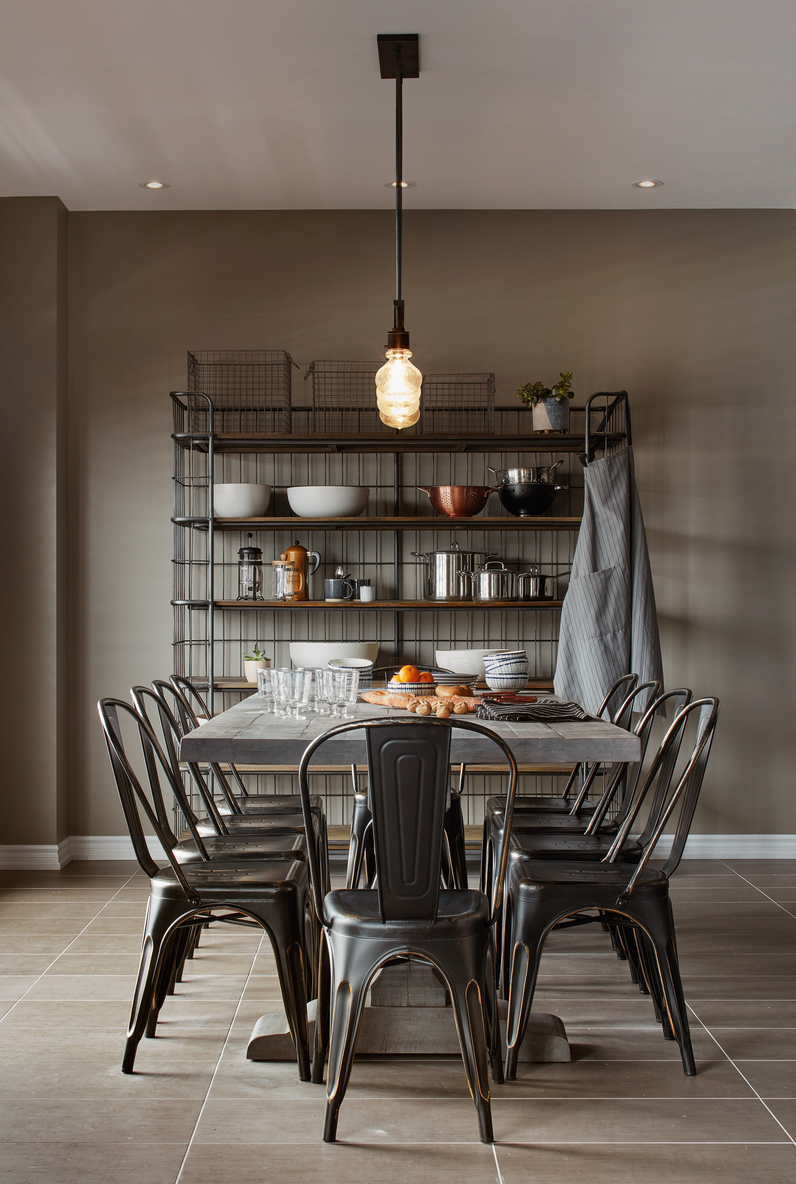 Industrial Ranch kitchen with large wood table, metal chairs, and industrial lighting