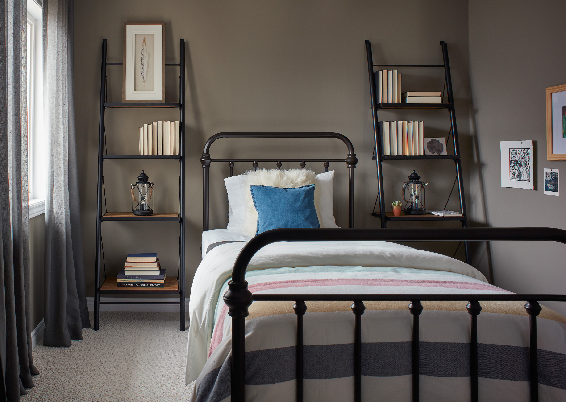 Industrial Ranch bedroom with black metal bed, grey-green walls, and ladder shelves against the wall