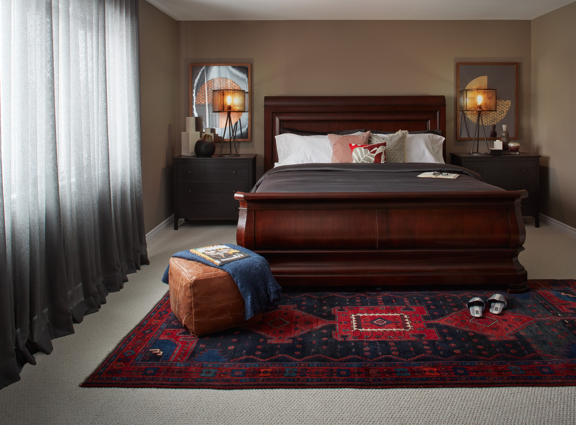 Industrial Ranch master bedroom with large mahogany bed and red patterned rug