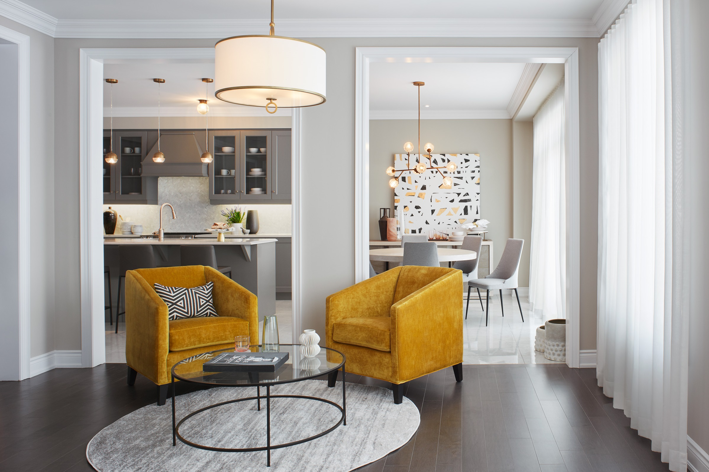Manor Estate living room with bright yellow armchairs, dark wood floors, and round rug
