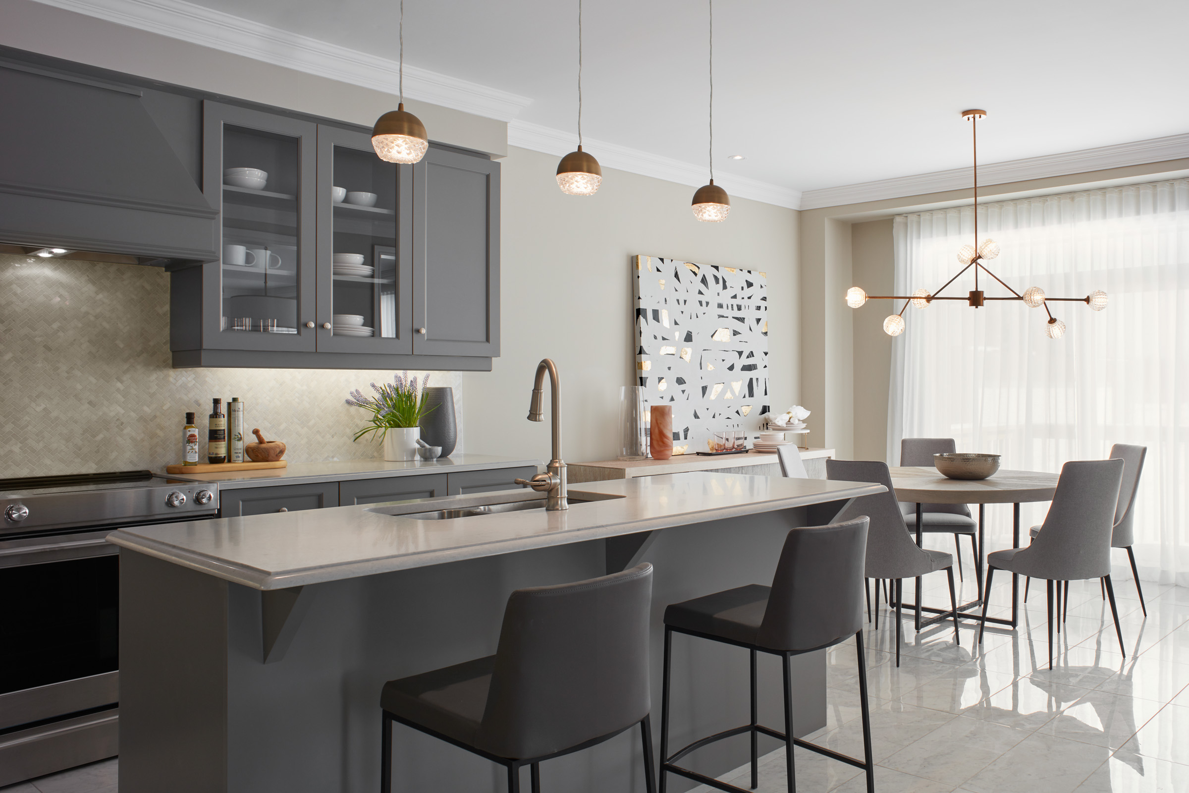 Manor Estate kitchen with island, grey cabinets, marble countertops, and brass light fixtures